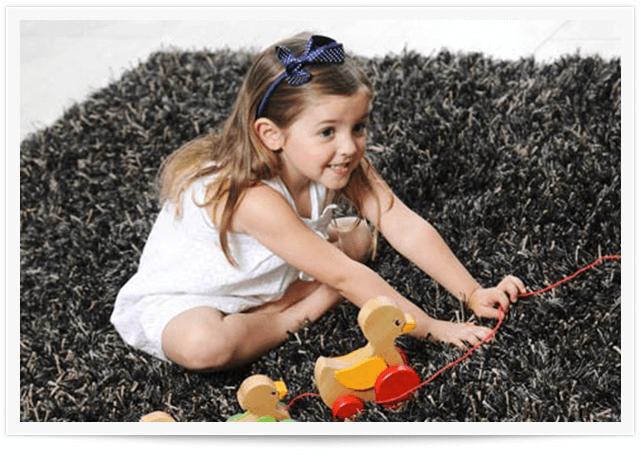 girl playing on gray area rug