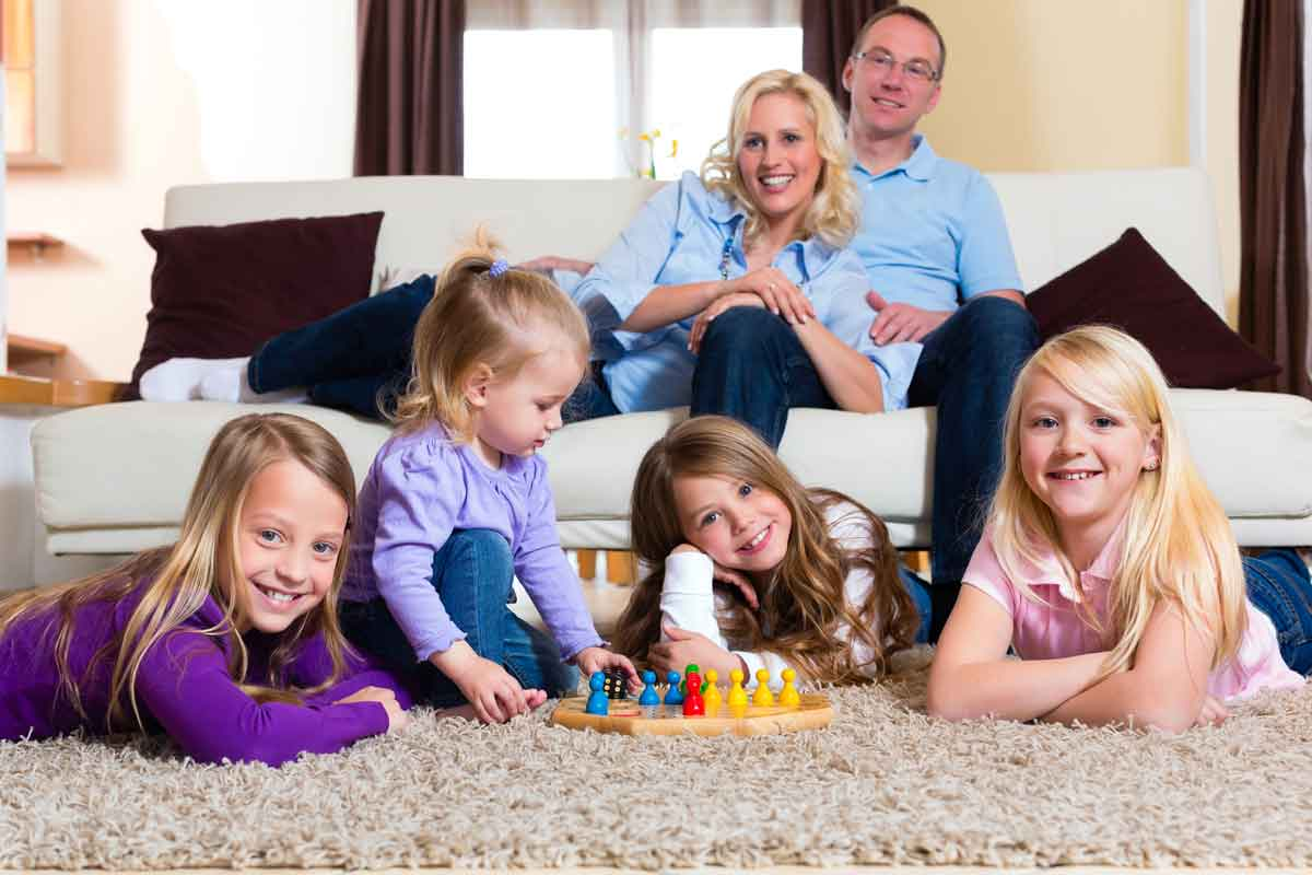 family playing on carpet in Orange county