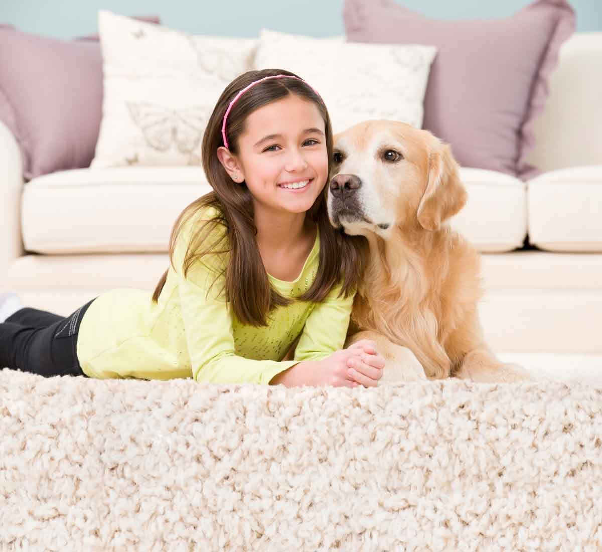 Girl and puppy laying on carpet
