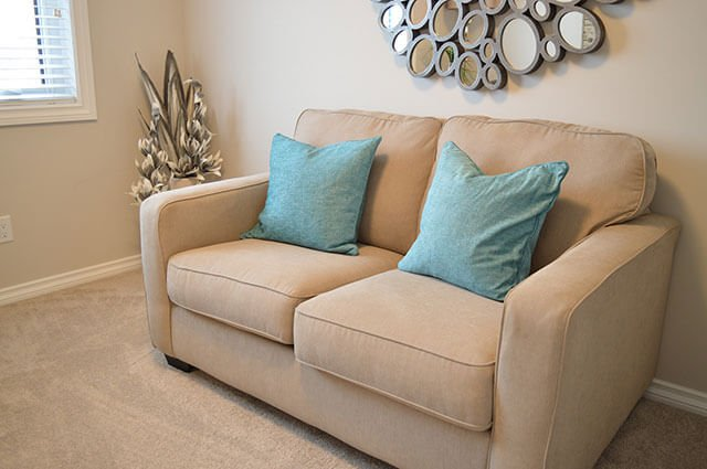 tan couch with blue pillows